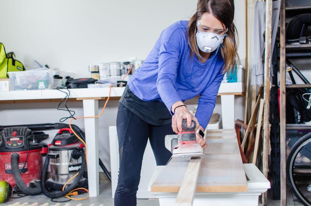 woman sanding slat wall boards