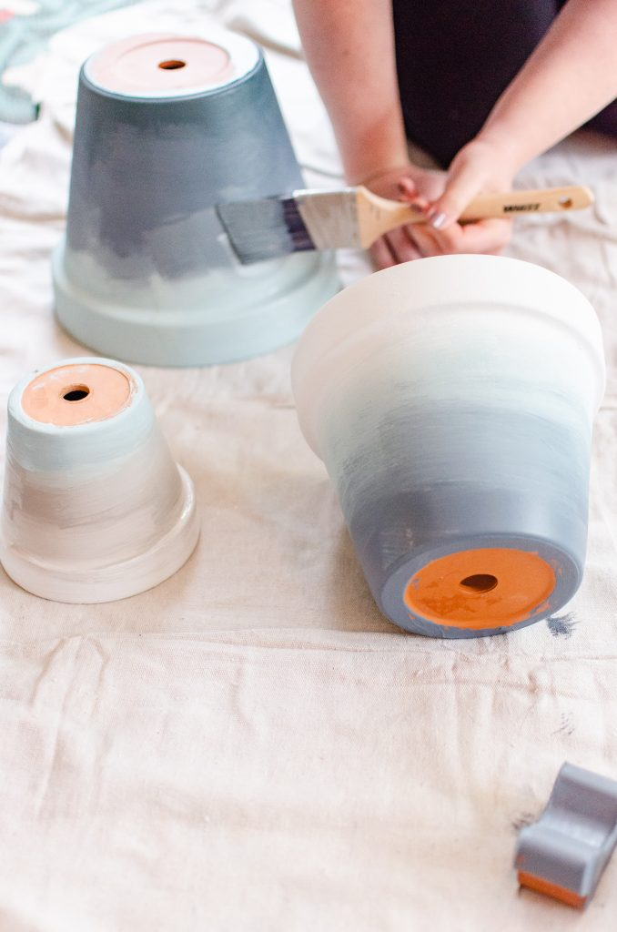 Ombre terracotta pots being painted with a paintbrush