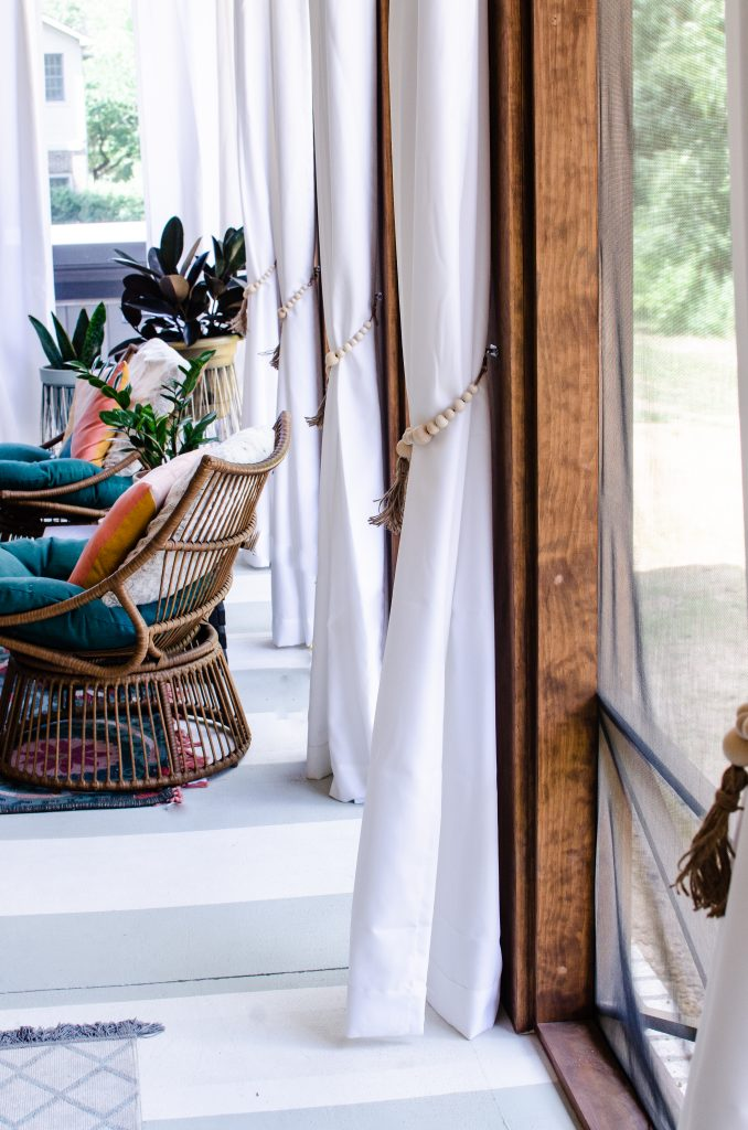 White curtains with wooded beaded tassel tie backs on back porch patio | HauteHouseLove.com