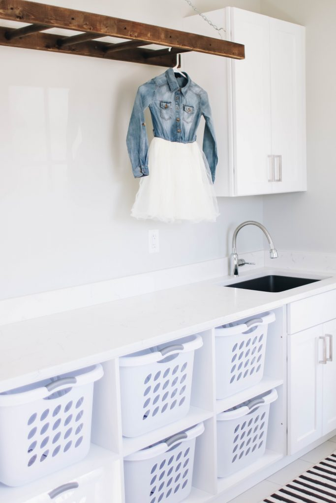 White Laundry Room design with cubbies for laundry baskers