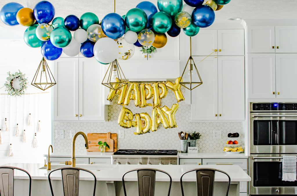 blue and green and gold balloon garland in kitchen