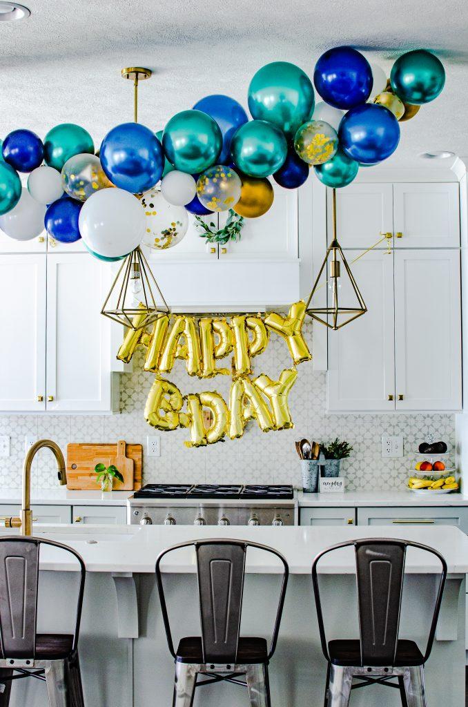 blue, green and gold birthday balloon garland in a white farmhouse kitchen