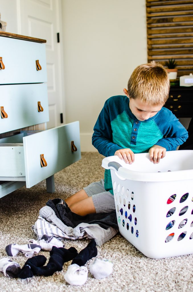 Child putting away clothes in organized drawers