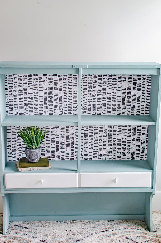Modern wallpaper that is used inside a light blue cabinet.