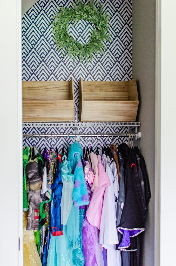blue geometric wallpaper accent wall in a dress up closet for kids