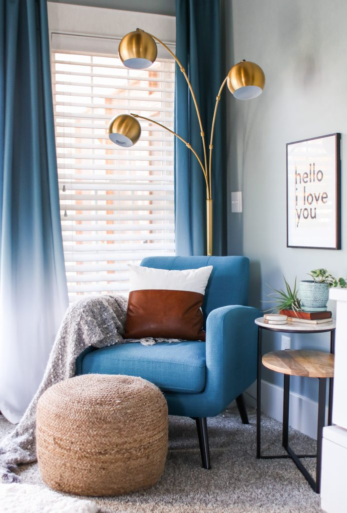 Master bedroom reading nook with blue chair and modern accents.