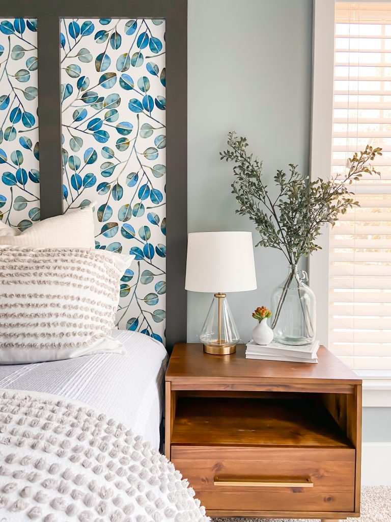 Wallpapered faux headboard with colorful printed wallpaper and warm wood side table.