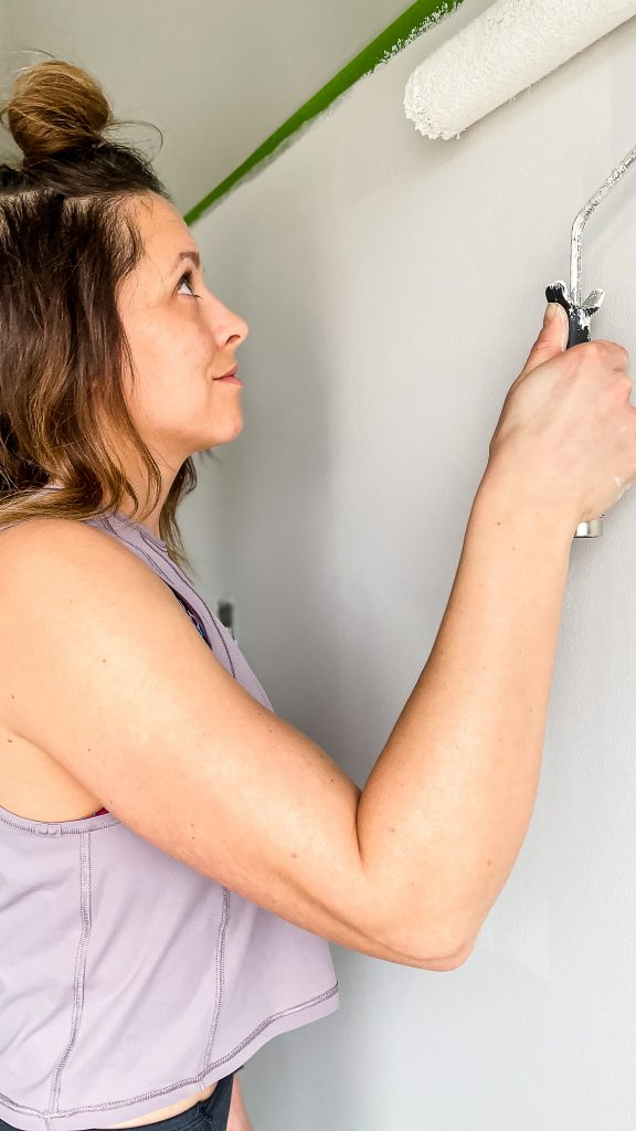 woman rolling a wall with white paint