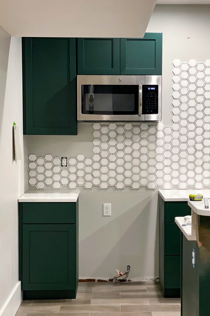 the kitchen wall partially tiled with Jeffrey Court Norton Mosaic