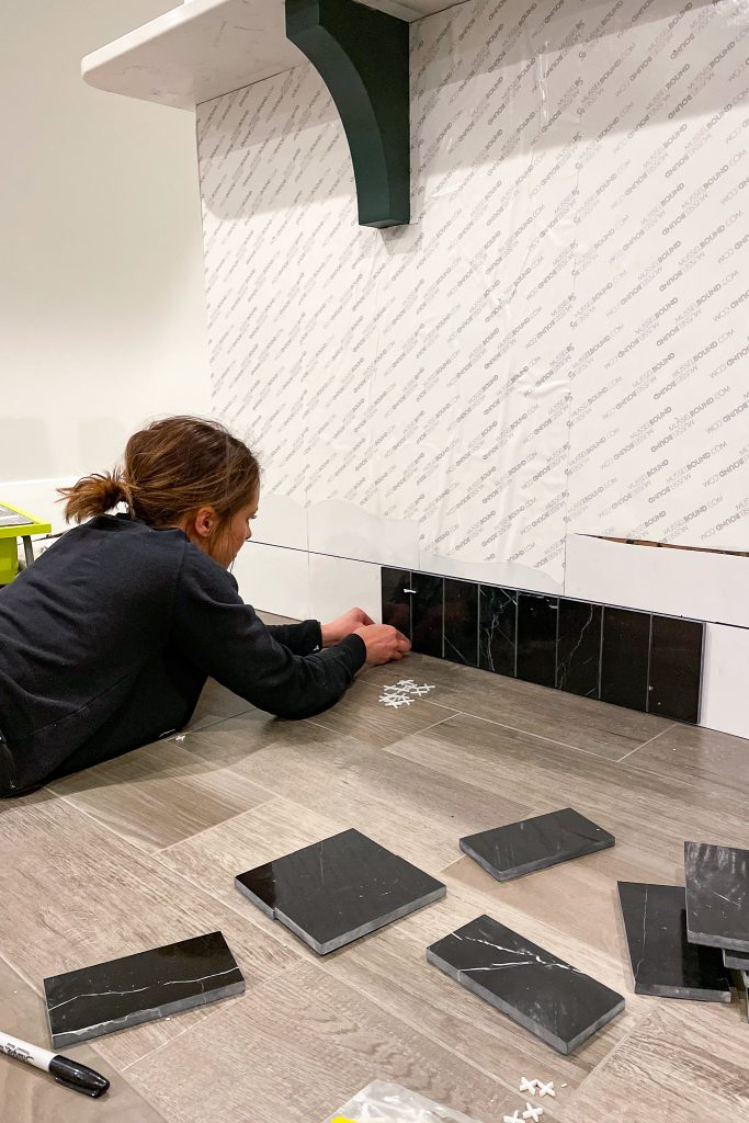 Laying the Nero Marquina tile on the back of the island with MusselBound