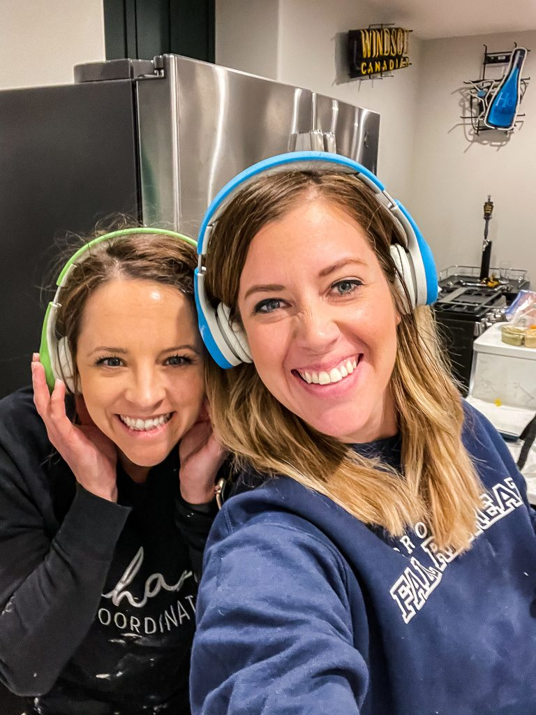 Emily and I wearing kids headphones because the tile saw is loud