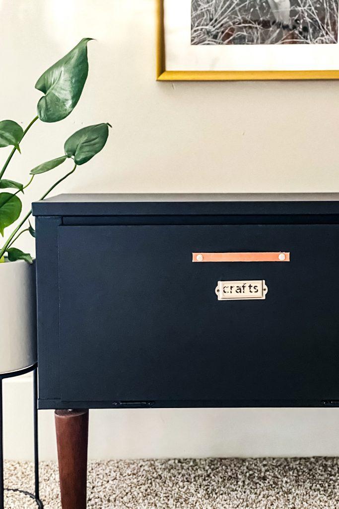 Playroom organization labels after. Wood Labels in metal label holder on a black storage cabinet.