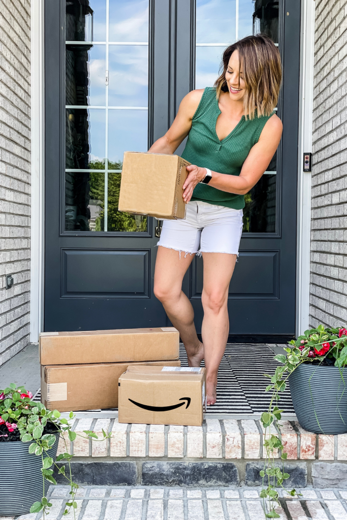 woman holding cardboard box with pile of more boxes at her feet on her front porch, one box is labeled as an Amazon box | Amazon Prime Day 2021 Finds on HauteHouseLove.com
