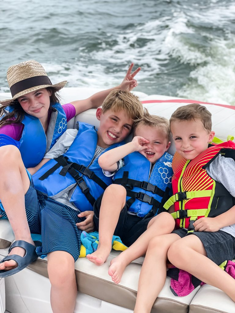 Four kids in life jackets on a boat in water, family vacation | Random Thoughts from The Weekender on HauteHouseLove.com