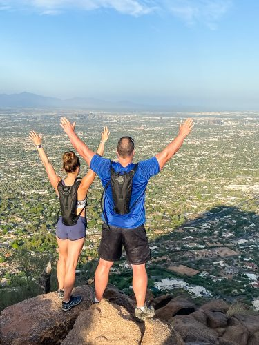 woman and man on the top of a mountain looking over a city with their arms raised above their heads   found on HauteHouseLove.com