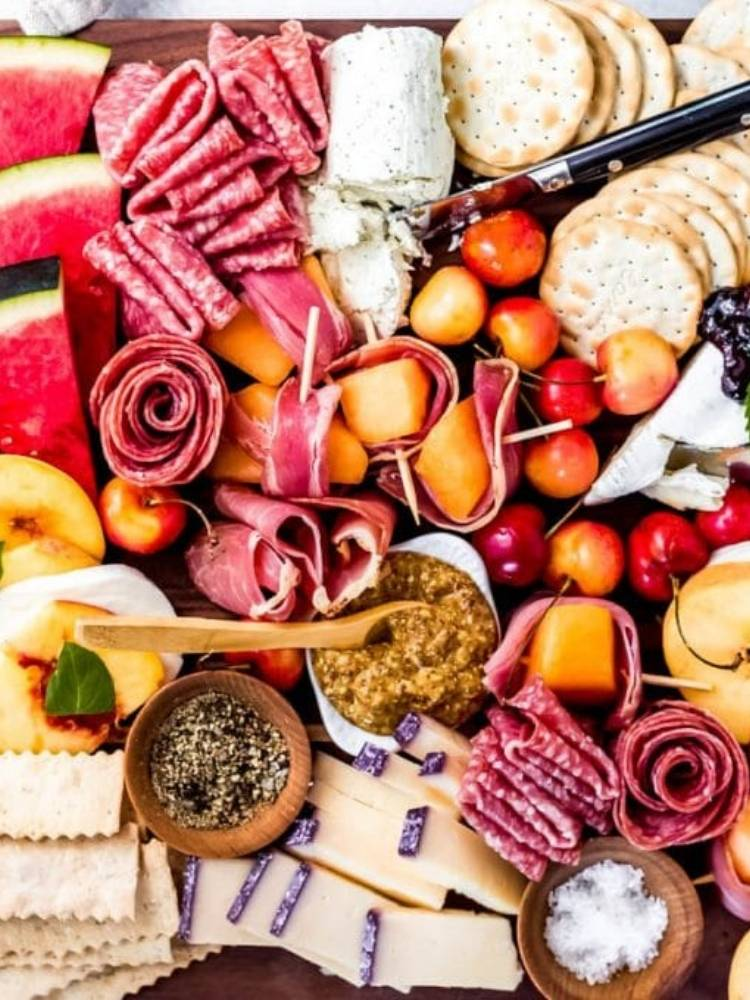 Close up of charcuterie board with meats, cheeses, and fruits