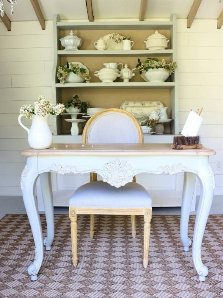 French country desk painted white with upholstered chair in front of a painted hutch filled with white dishes