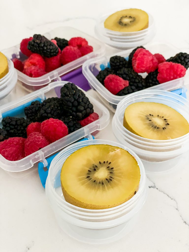 Fresh berries and kiwi in storage containers for lunch boxes