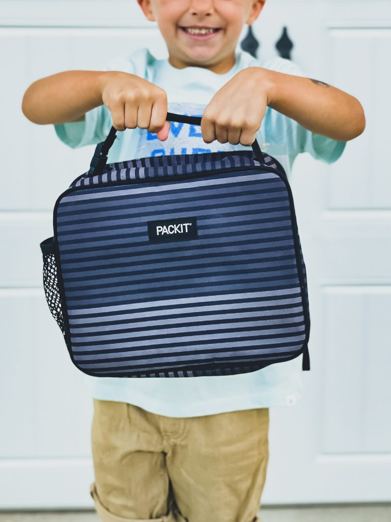 Young boy holding blue striped lunchbox   HauteHouseLove.com